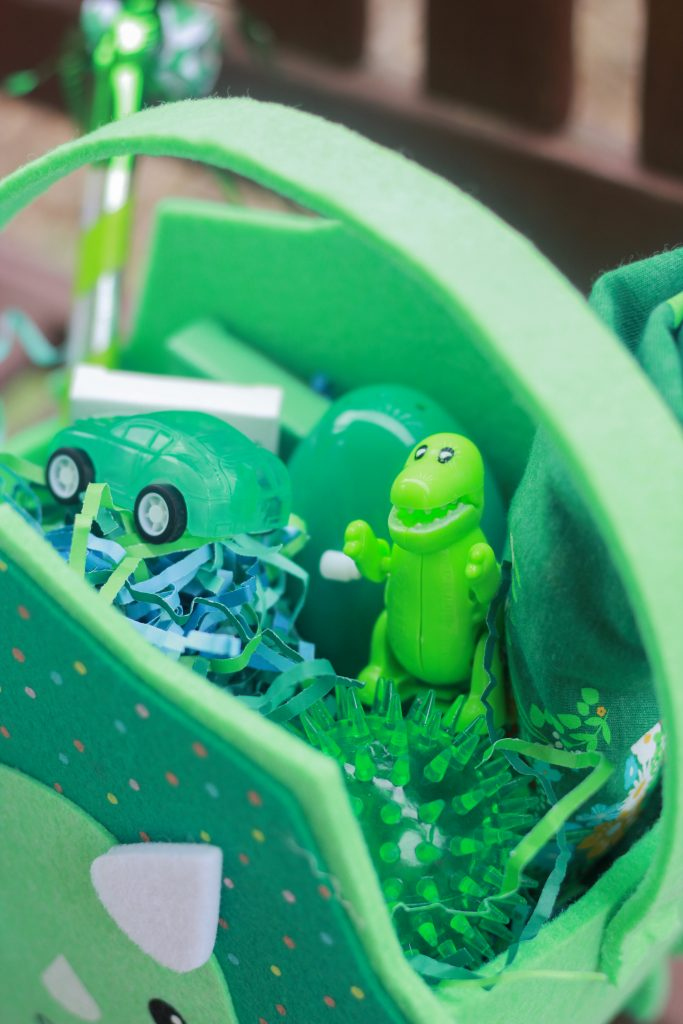 Close up of Easter basket showing a wind up toy dino, toy care, and spiked light up ball.
