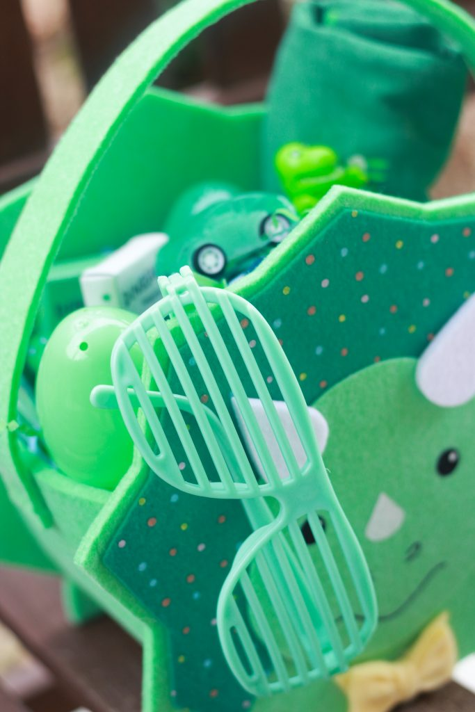 Close-up of dinosaur Easter basket with items like sunglasses, toy care, and toy dinosaur.