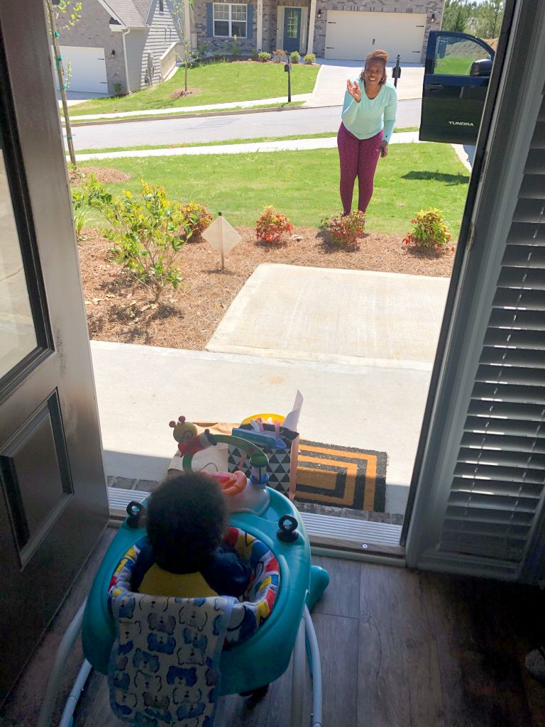 Grandparent standing at a 6 feet distance waving at her grandchild.