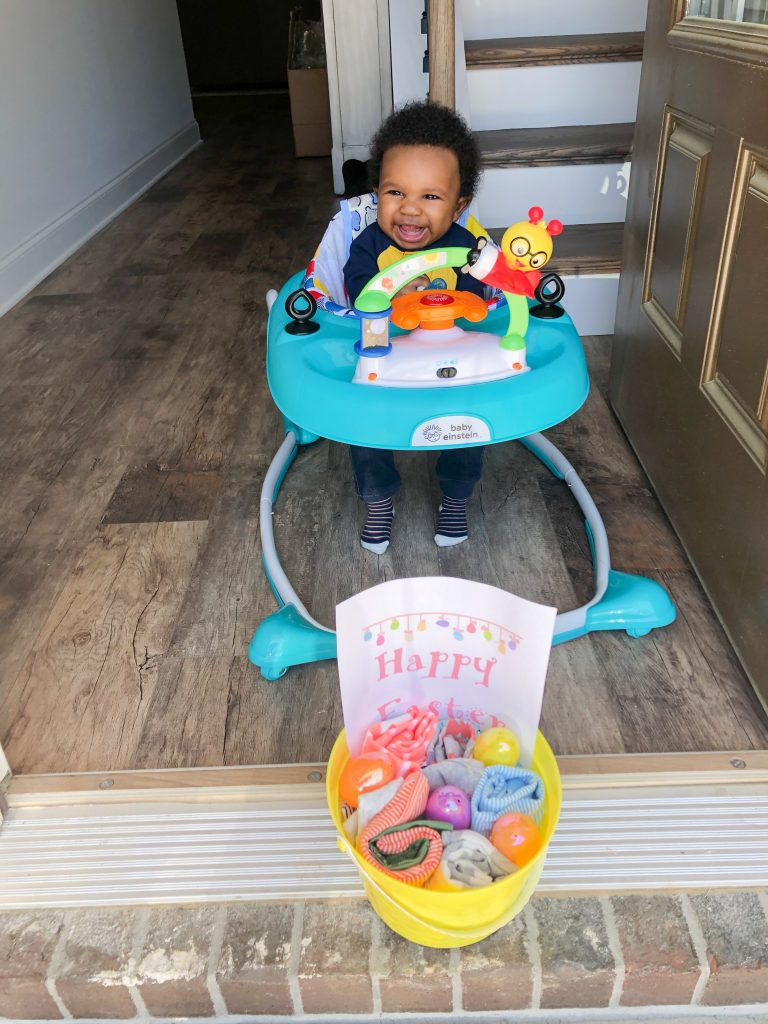 4 month old EJ sitting in his baby Einstein walker with his first Easter basket provided by his grandparents.