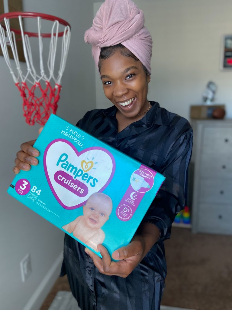 Black female mother holding a size 3 Pampers cruisers box.