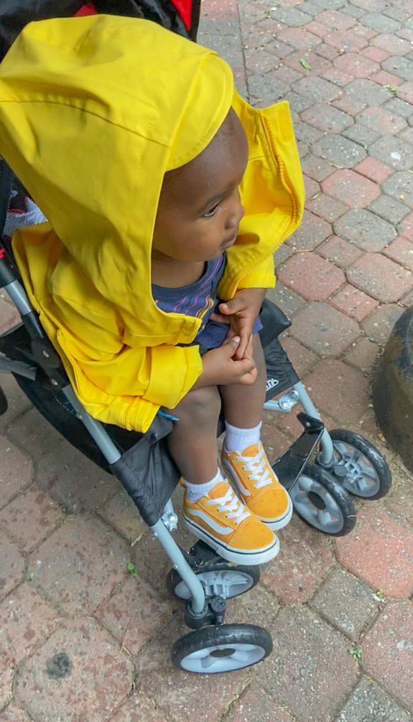 Toddler wearing a yellow rain jacket while sitting in an umbrella stroller at Zoo Atlanta.